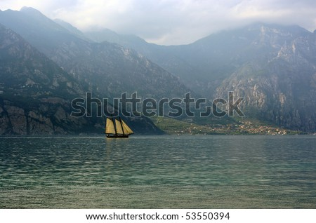 Sail boat on a lake with mountains as a background - stock photo