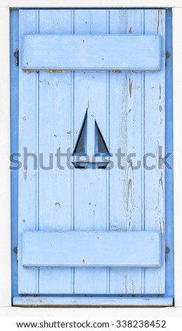Sail boat on blue wooden shutter - stock photo