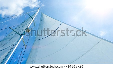 sail of a boat with light blue sky sunny day background.