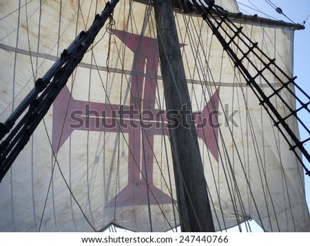 Sail of a caravel ship with red cross - stock photo