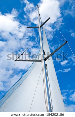 sail yacht mast with white sail against blue sky  - stock photo