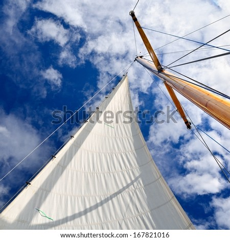 sail yacht mast with white sail against dark blue sky - stock photo