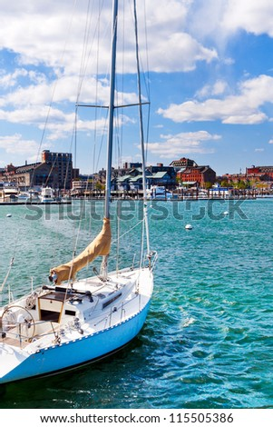 Sailboat anchored in the Boston harbor with a view facing the waterfront and city skyline.  Beautiful day with blue sky, bright sunlight and puffy white clouds. - stock photo
