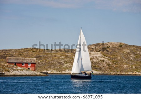 Sailboat and rocky coastline - stock photo