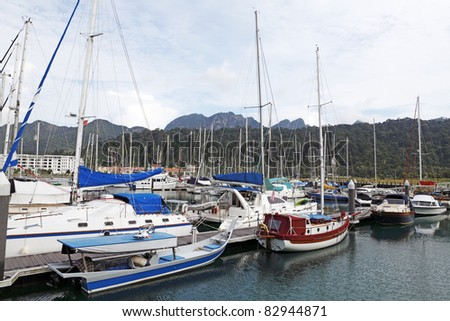 Sailboat and yacht docked at a coastal marina in Langkawi Island, Malaysia, overlooking  green hills against a dramatic morning sky. - stock photo