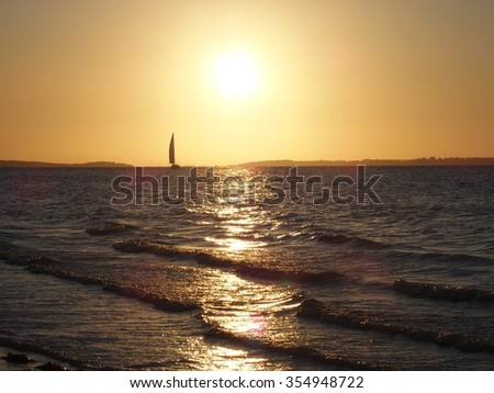 Sailboat at beach sunset with lapping waves - stock photo