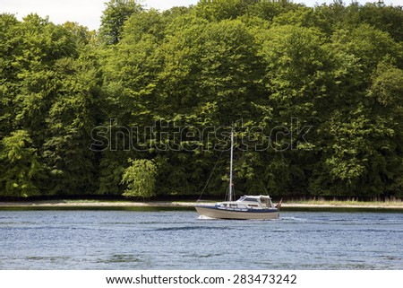 Sailboat close to springtime green forest in Denmark - stock photo
