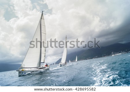 """Sailboat coming one after the other with a large roll. Tivat, Montenegro - 26 April, 2016. Regatta """"Russian stream"""" in God-Katorskaya bay of the Adriatic Sea off the coast of Montenegro. - stock photo"""