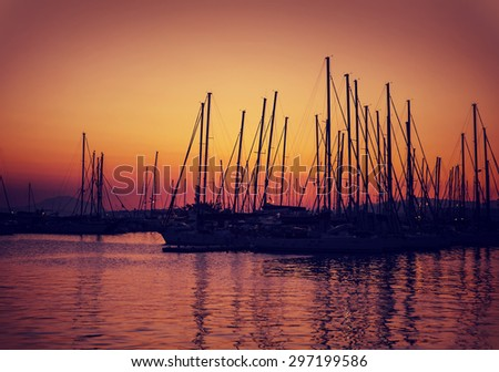 Sailboat harbor on sunset, silhouettes of luxury water transport in red and yellow evening sun light, beautiful view on port in Greece - stock photo