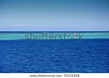 Sailboat in the middle of the ocean with beautiful colours - stock photo