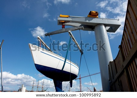 Sailboat lift up by a heavy industrial boat lifter for maintenance - stock photo
