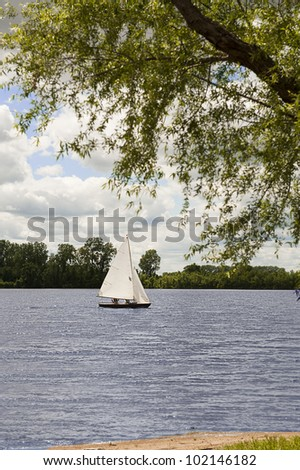 Sailboat makes its way across Creve Coeur Lake on a cloudy day - stock photo