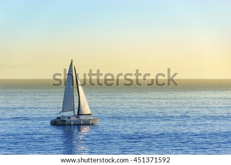 Sailboat on in the sunset gliding over the calm ocean surface.
