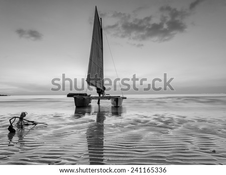sailboat on the beach with a beautiful sunset in black and white