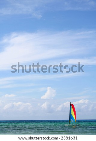 sailboat on the caribbean sea, sunny day with clouds above - stock photo