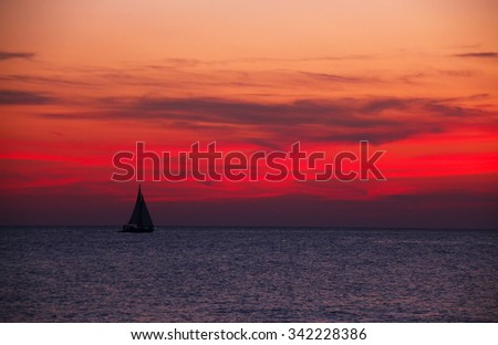 Sailboat on the ocean at bloody red sunset - stock photo