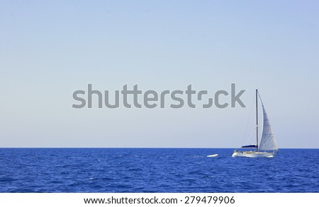 Sailboat on Vast Blue Ocean Sailing in front of Big Blue Sky on Sunny Day, with Copy Space - stock photo