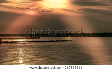 Sailboat sailing home under a golden sunset on the Chesapeake bay in Maryland - stock photo