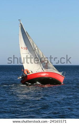 Sailboat sailing in the morning at a deep blue sea - stock photo