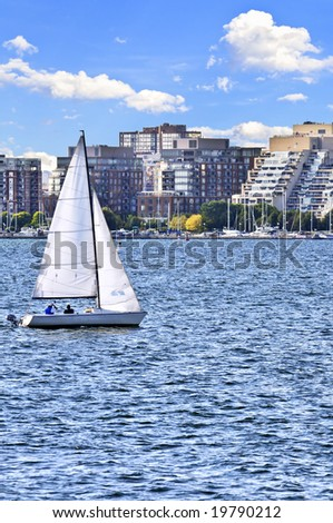 Sailboat sailing in Toronto harbor with scenic waterfront view - stock photo
