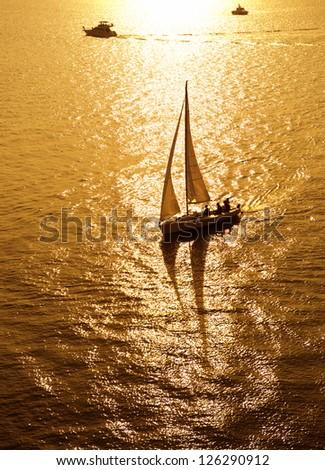 sailboat sailing sailing at the sea with a beautiful sunset. - stock photo