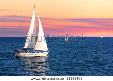 Sailboat sailing towards sunset on a calm evening - stock photo
