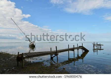 Sailboat stranded on the beach after a storm - stock photo