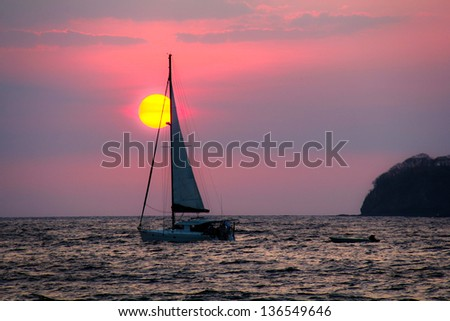 Sailboat Sunset Costa Rica. A lone sailboat against a sunset in the pacific ocean off the coast of Costa Rica. - stock photo