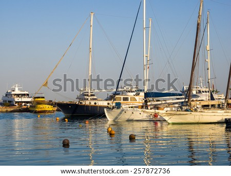 Sailboats and motorboats in sea harbor. Beautiful yachts are moored at pier. Water transport for luxury lifestyle in summertime and sea vacation.