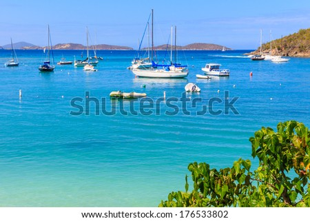 Sailboats and power boats anchored in crystal clear turquoise waters in the Caribbean - stock photo