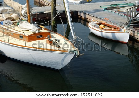 Sailboats and small skiff sitting in calm waters at a local new england dock - stock photo