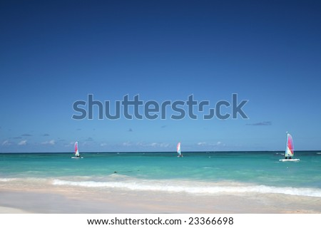 Sailboats in ocean - Beautiful Caribbean tropical beach with white sand and green waves. FOCUS on sailboats - stock photo