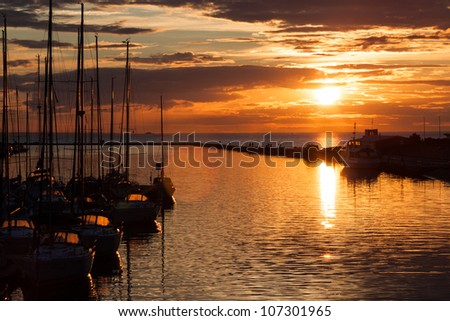 Sailboats silhouette in harbor with sunset and clouds