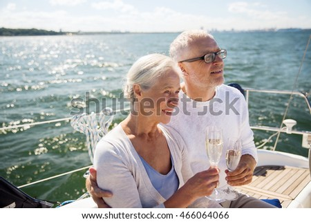 sailing, age, tourism, travel and people concept - happy senior couple drinking champagne on sail boat or yacht deck floating in sea