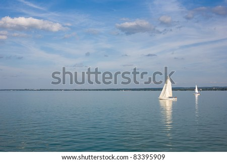 Sailing away on blue waters with strip of land behind.