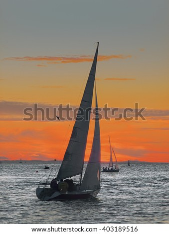 Sailing boat and the people, located in her, on a background of the sunset are visible as outline profiles. - stock photo