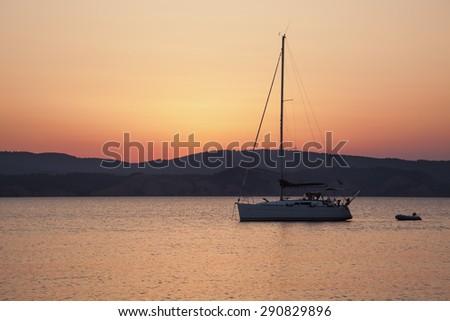 Sailing boat at sunset - stock photo