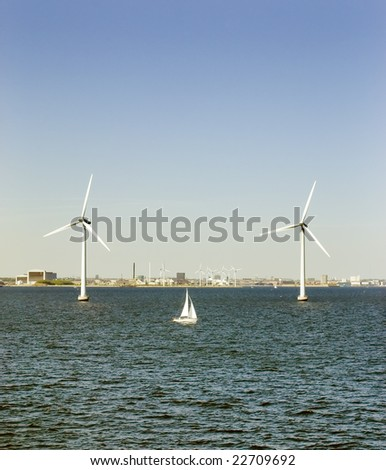 sailing boat between two wind turbines