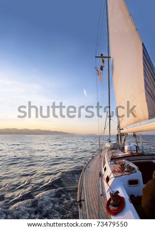 Sailing boat in the sea at the dawn - stock photo