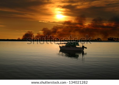 Sailing boat moored with a wild fire burning in the background. - stock photo