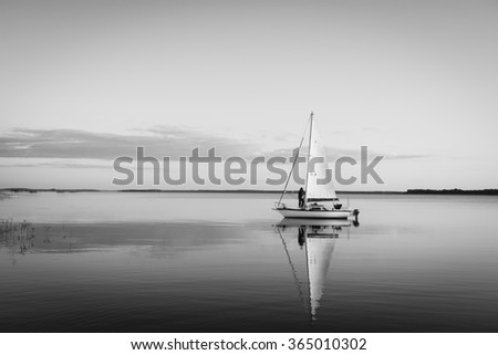 Sailing boat on a calm lake with reflection in the water. Serene scene landscape. Black and white horizontal photograph. - stock photo