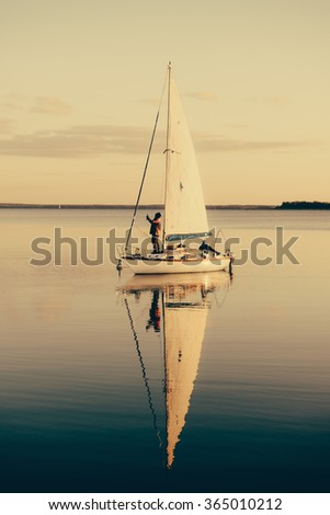 Sailing boat on a calm lake with reflection in the water. Serene scene landscape. Vertical vintage effect  photograph. - stock photo