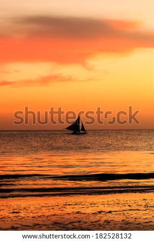 Sailing boat on a calm ocean after a tropical sunset - stock photo