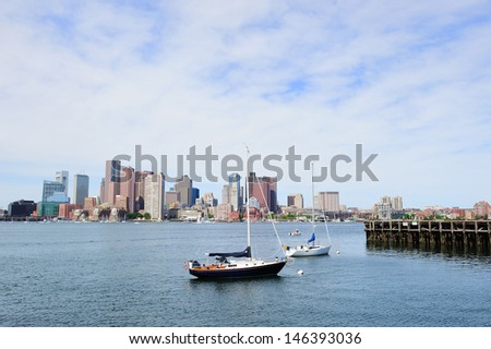 Sailing boat rest with dock in bay and Boston downtown skyline with urban skyscrapers over sea in the morning.