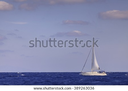 Sailing boat with mainsail in open blue sea - stock photo