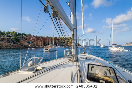 Sailing boats at anchorage in calm bay, view from deck. Ibiza, Spain - stock photo