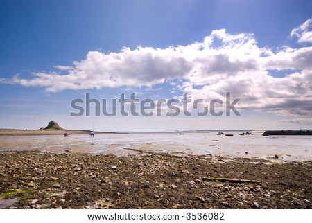Sailing boats in Holy Island harbour overlooked by Lindisfarne Castle - stock photo