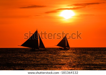 Sailing boats in silhouette against a tropical sunset - stock photo
