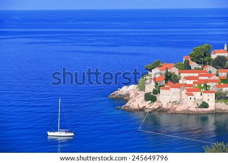 Sailing boats on the blue sea \round old Mediterranean resort, Sveti Stefan, Montenegro - stock photo