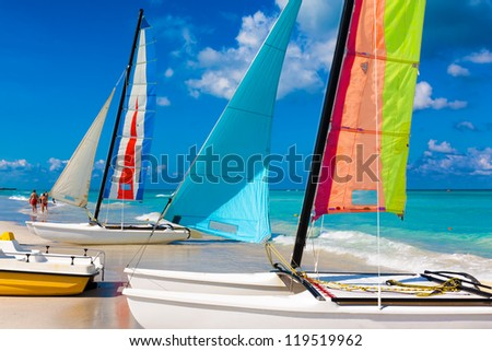 Sailing boats with its colorful sails spread out on Varadero beach in Cuba - stock photo
